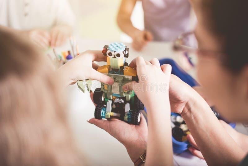 Kind en vrouwenwapens die robot maken stock afbeelding