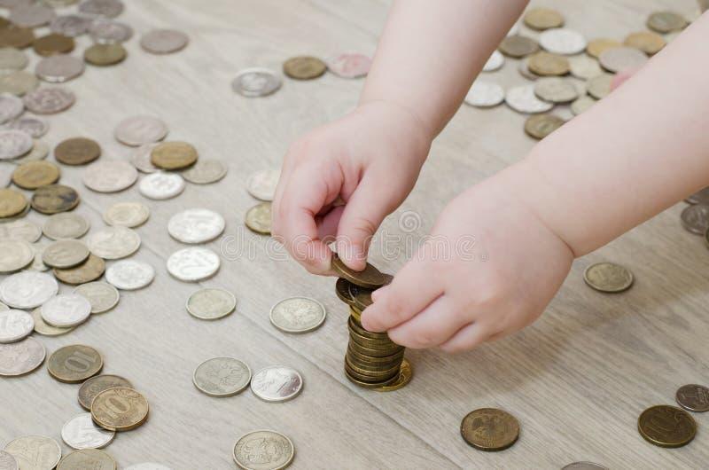 Kind errichtet einen Turm von Münzen lizenzfreie stockfotos