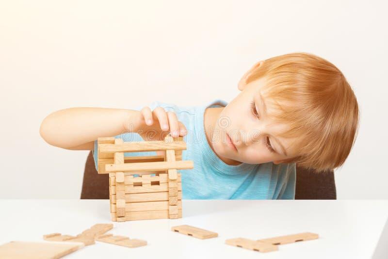 Kind errichtet kleines Holzhaus Eco Haus Goldtasten in den Fingern mit Häusern Wenig Jungenspiele mit Blöcken Kindheit und Entwic stockfotografie