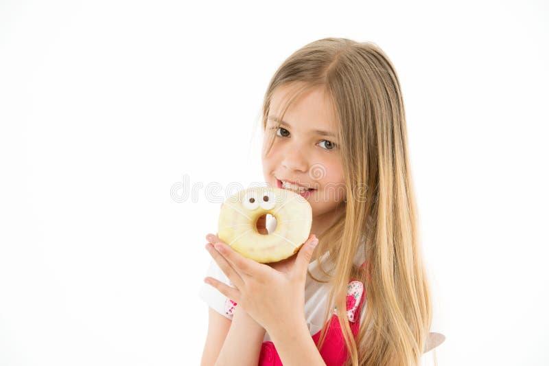 Kind essen den Donut, der auf Weiß lokalisiert wird Kleines Mädchen mit glasig-glänzendem Ringdonut Kind mit ungesunder Fertigkos stockbild