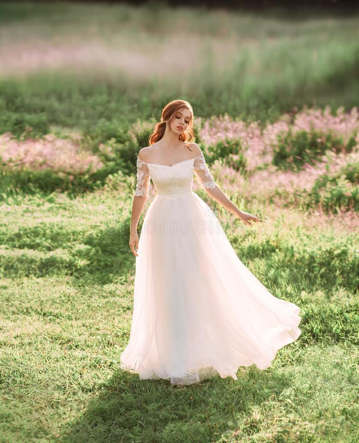 A kind fairy in a white dress is dancing in a clearing of beautiful pink flowers. graceful princess. freedom and royalty free stock images