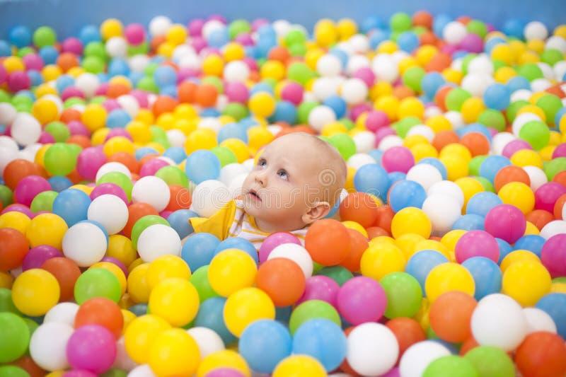 Kind in farbigen Bällen stockbild