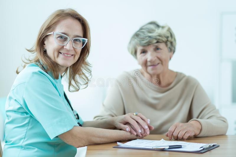 Kind female medic with patient. Picture of kind female medic with her aged patient stock photos