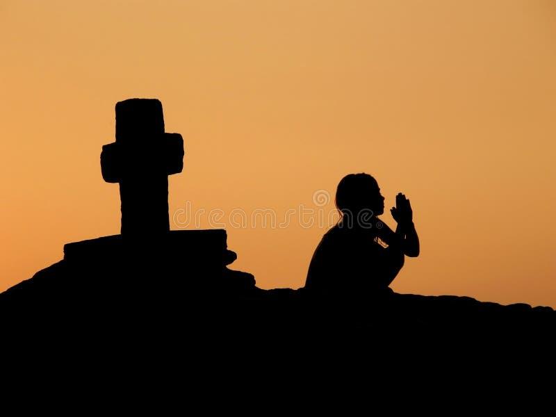 Kind, gebed, kruis in zonsondergang stock foto
