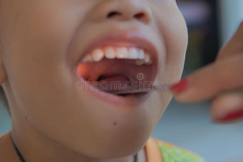 Kind geduldige Controle de amandel door arts in het ziekenhuis stock foto's