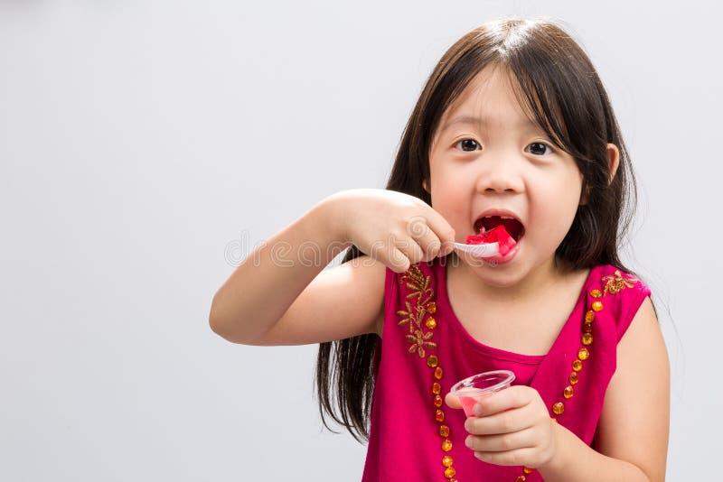 Kind Gelatinedessert eten/Kind die de Achtergrond van het Gelatinedessert eten stock foto