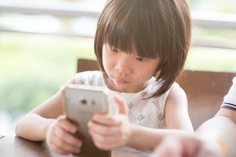 Kind gewöhnt zum intelligenten Telefon lizenzfreie stockfotografie