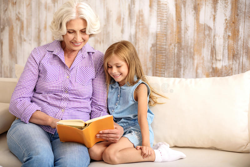 Kind granny and girl entertaining with book at home royalty free stock images