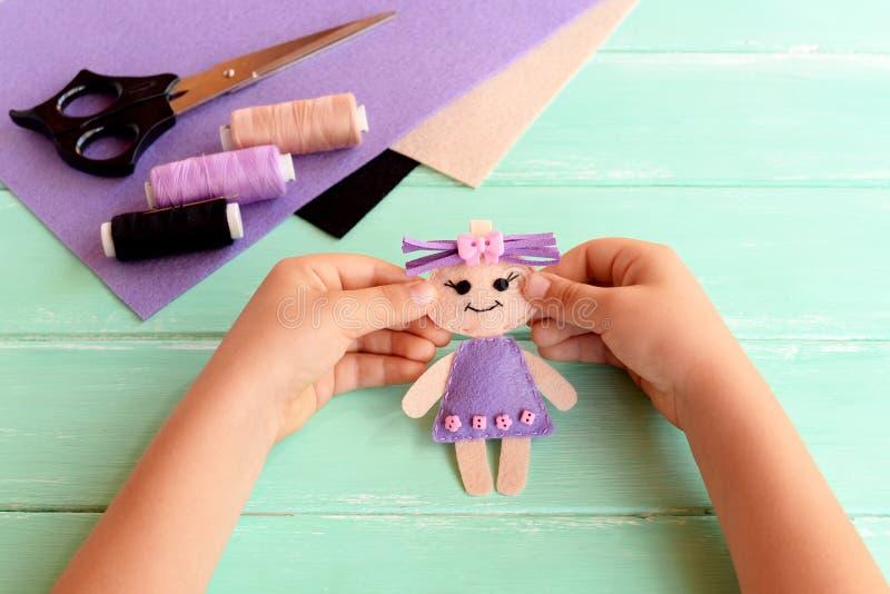 Kind hält eine Filzpuppe in seinen Händen und zeigt sie Scheren, Thread, Filz bedeckt auf einer Tabelle Nettes angefülltes Spielz lizenzfreie stockfotos