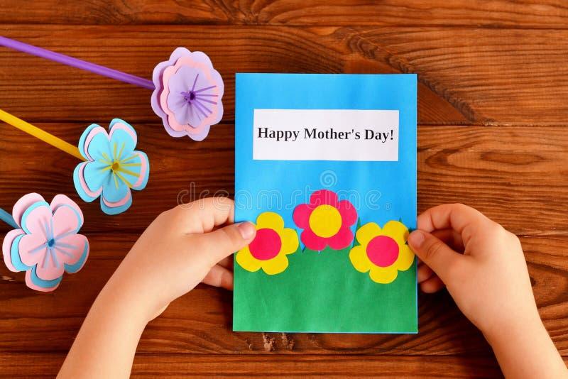 Kind hält eine Karte in seiner Hand Glücklicher Tag des Mutter Ein Blumenstrauß der Blumen Das Handwerk der Kinder für Muttertag stockfotografie