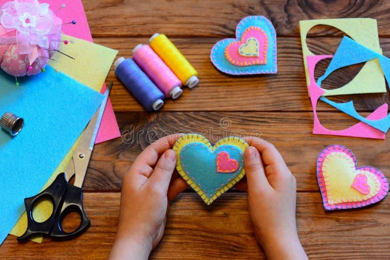 Kind hält einen Filzvalentinsgruß in seinen Händen Kind machte Valentinsgrüße vom Filz Valentinsgrußtag macht Idee in Handarbeit  lizenzfreie stockfotografie