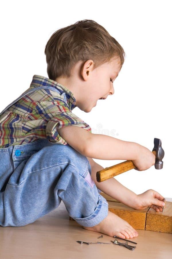 Kind hämmert einen Hammer in den Nägeln lizenzfreie stockfotos