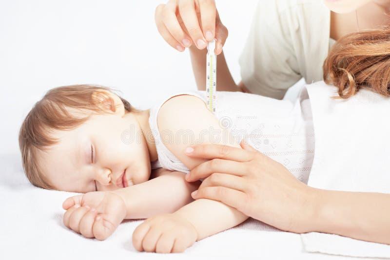Kind hat eine hohe Temperatur oder ein Fieber, unter Verwendung eines Thermometers lizenzfreies stockbild