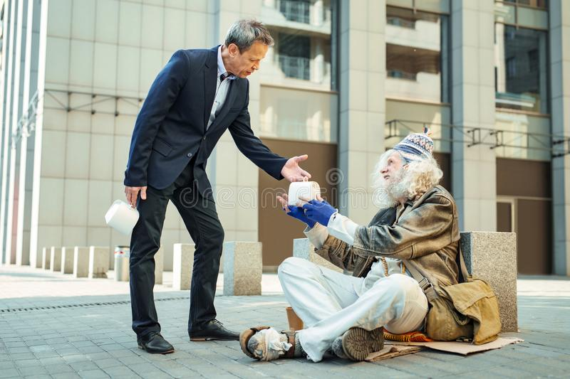 Kind-hearted charity man giving some food to poor refugee royalty free stock image