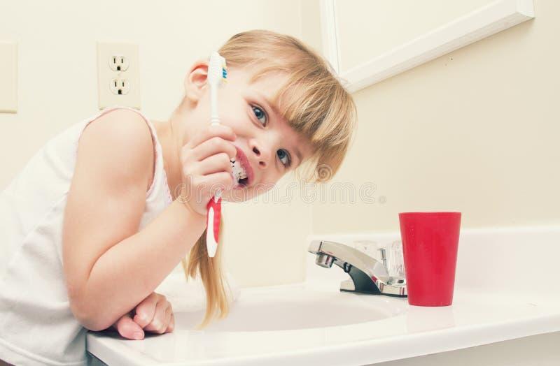 Kind het borstelen tanden in badkamers stock afbeelding