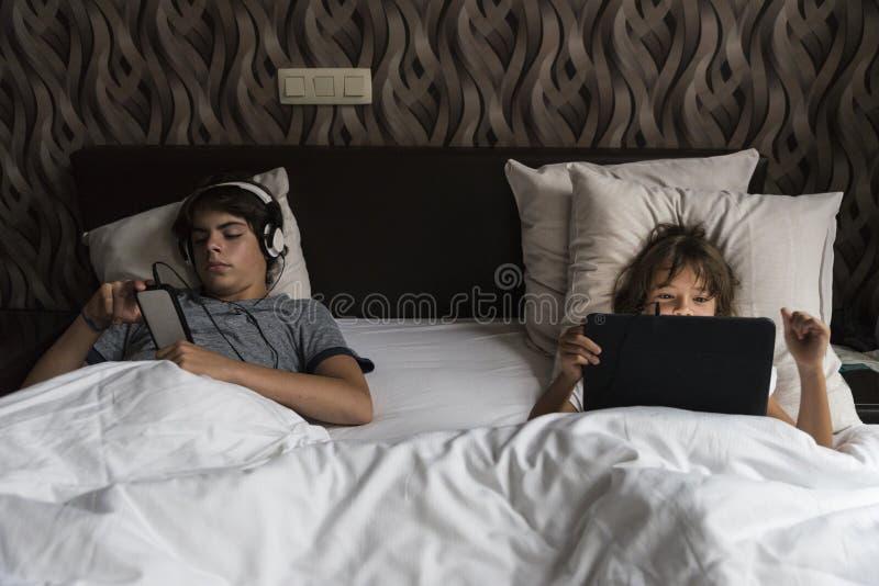 Kind het ontspannen met slimme telefoon en een digitale tablet royalty-vrije stock afbeelding
