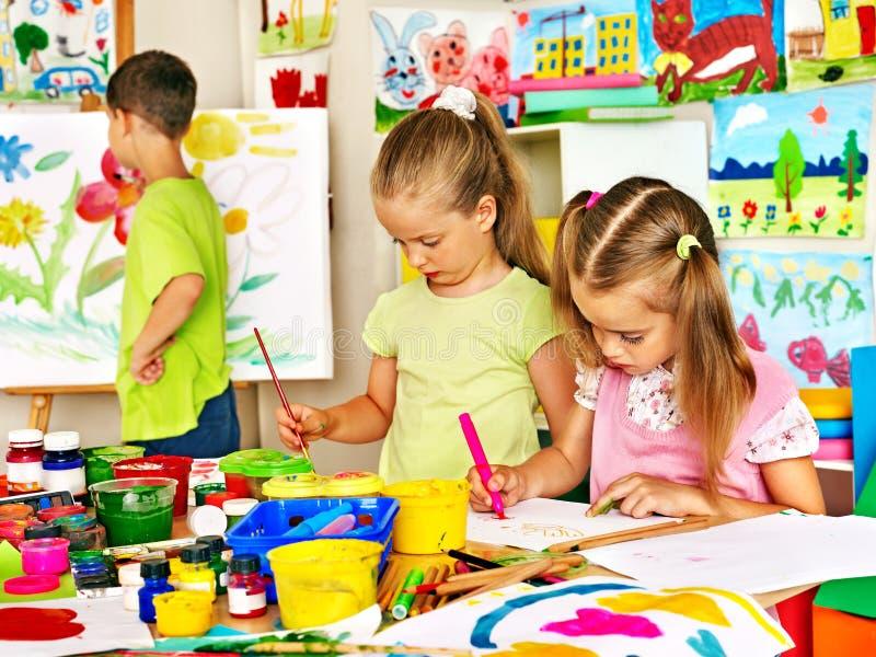 Kind het schilderen bij schildersezel stock afbeeldingen