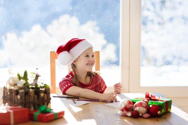 Kind het schrijven brief aan santa Onderhavige wenslijst stock foto