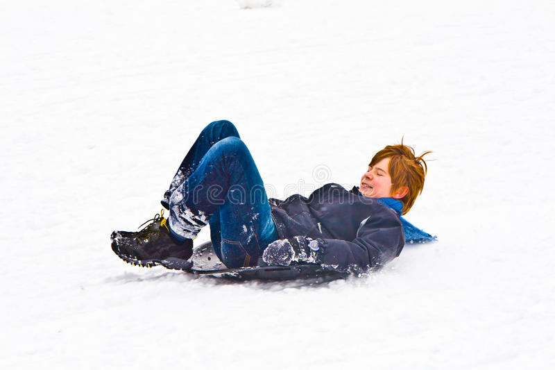 Kind het sledging onderaan de heuvel in sneeuw stock foto's