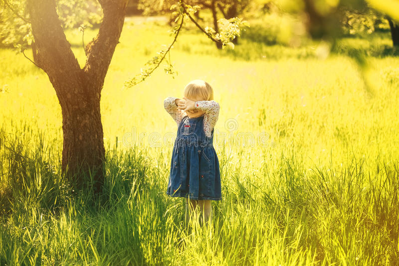 Kind het spelen alleen in zonnige tuin stock foto's