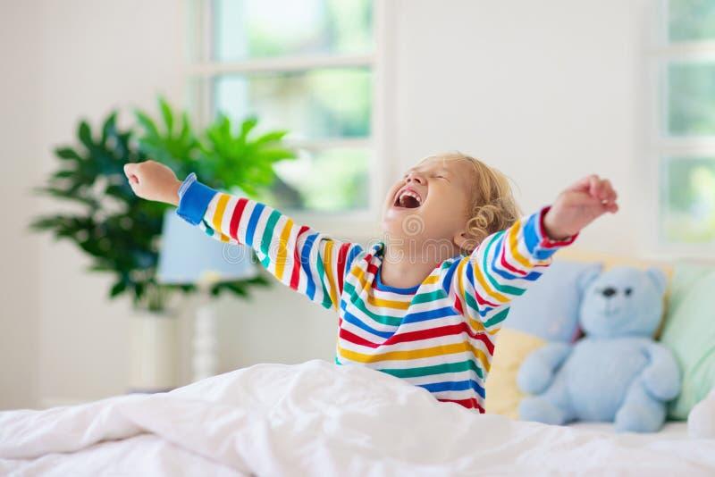 Kind het spelen in bed De ruimte van jonge geitjes Babyjongen thuis royalty-vrije stock foto's