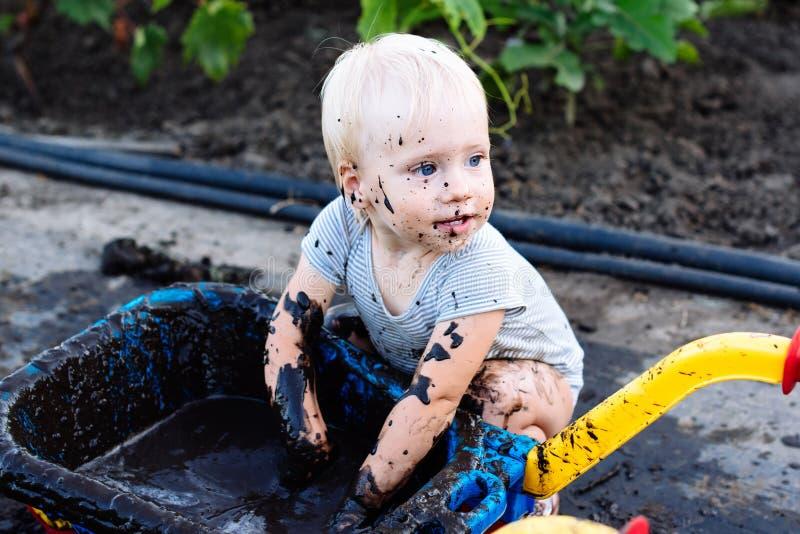 kind het spelen in de modder op de straat stock fotografie