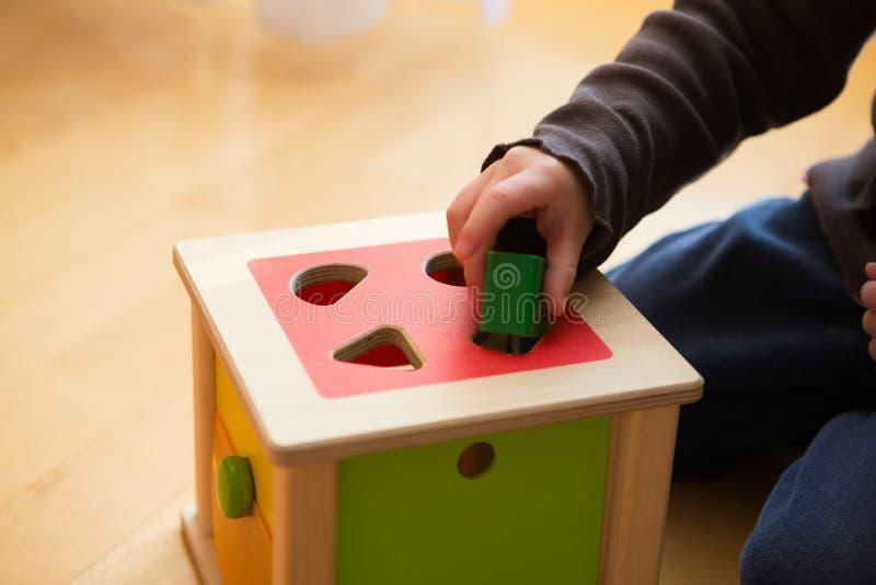 Kind het spelen met houten bakstenen die in verschillende vormen en kleuren hen in het juiste gat proberen te zetten stock afbeelding
