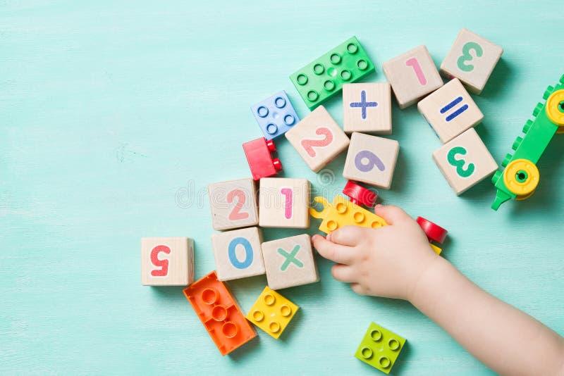 Kind het spelen met houten kubussen met aantallen en kleurrijke stuk speelgoed bakstenen op een turkooise houten achtergrond stock foto's