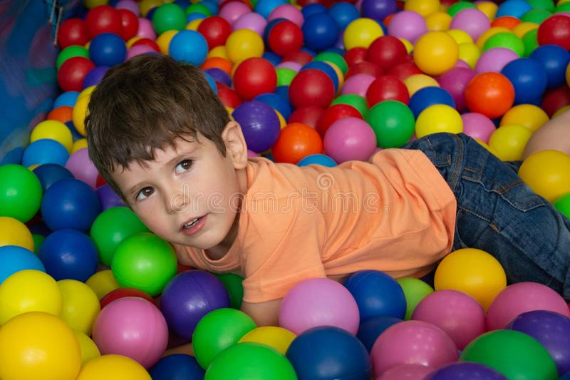 Kind het spelen met kleurrijke ballen in de pool van de speelplaatsbal Activiteitenspeelgoed voor weinig jong geitje De emotie di royalty-vrije stock foto
