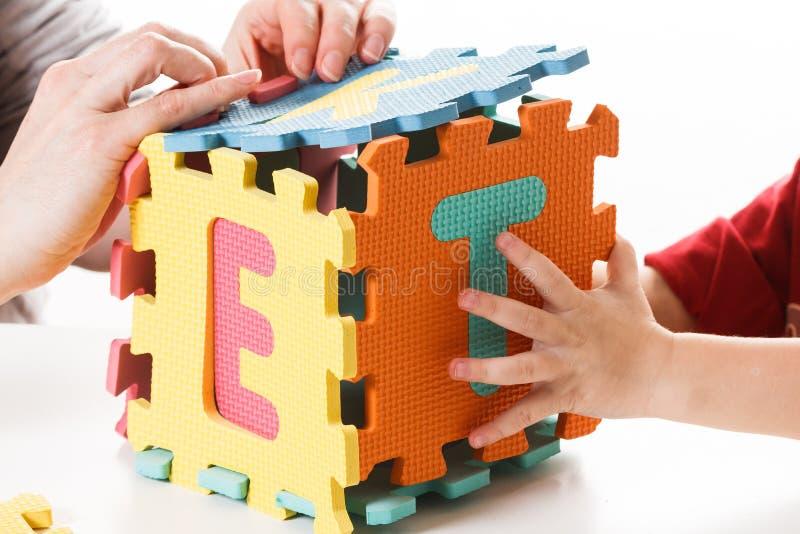 Kind het spelen met raadsel blokkeert abc kleurrijk alfabet, stock fotografie