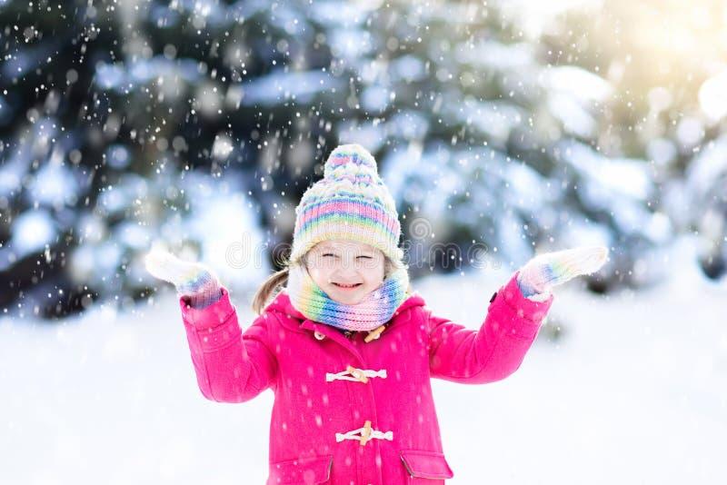 Kind het spelen met sneeuw in de winter Jonge geitjes in openlucht stock afbeelding