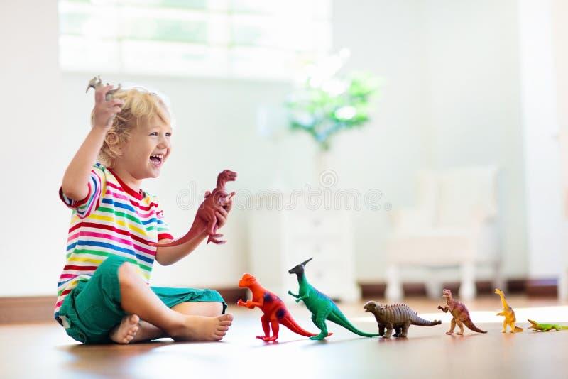 Kind het spelen met stuk speelgoed dinosaurussen Jonge geitjesspeelgoed royalty-vrije stock afbeeldingen