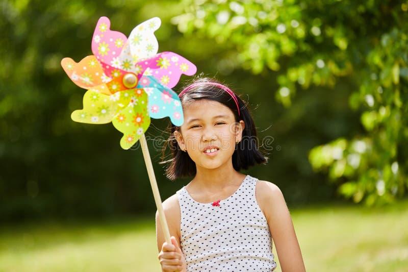 Kind het spelen met windmolen stock afbeelding