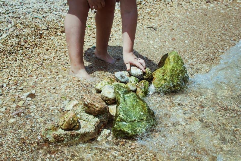 Kind het spelen op de strand en de bouw steentoren Stenen op het strand royalty-vrije stock foto's