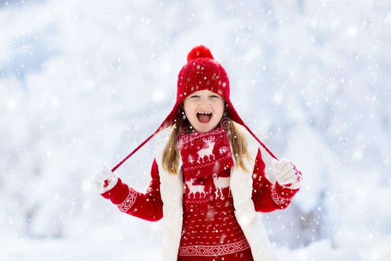 Kind het spelen in sneeuw op Kerstmis Jonge geitjes in de winter stock foto