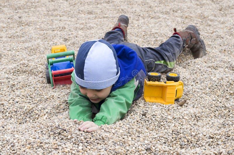 Kind het spelen in stenenkiezelstenen bij speelplaats stock foto's