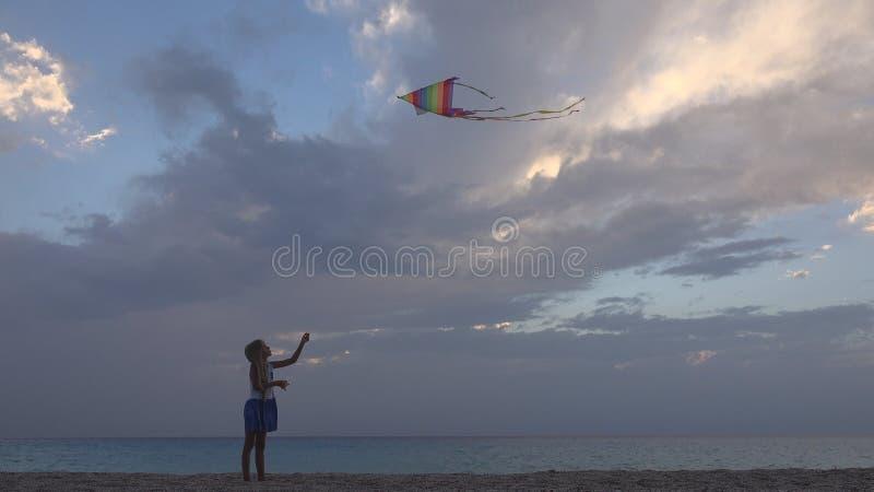 Kind het Spelen Vliegende Vlieger op Strand bij Zonsondergang, Gelukkig Meisje op Kustlijn royalty-vrije stock afbeeldingen