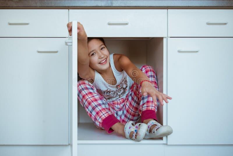 Kind het verbergen in de keukenkast, die uit haar vingers plakken zoals is wil zij somebody doen schrikken royalty-vrije stock fotografie