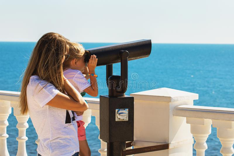 Kind in ihren Mutterarmen betrachtet das Meer durch Ferngläser lizenzfreie stockfotografie