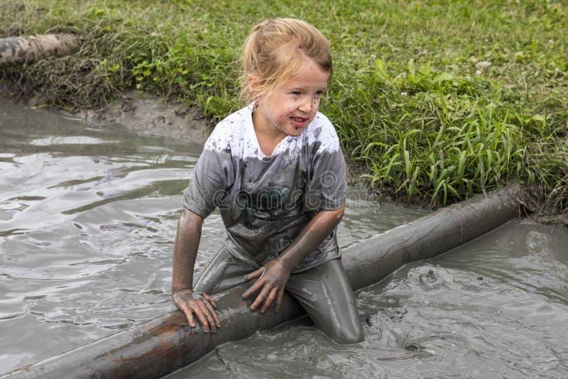 Kind im Abzugsgraben im Schlamm-Rennen lizenzfreies stockbild