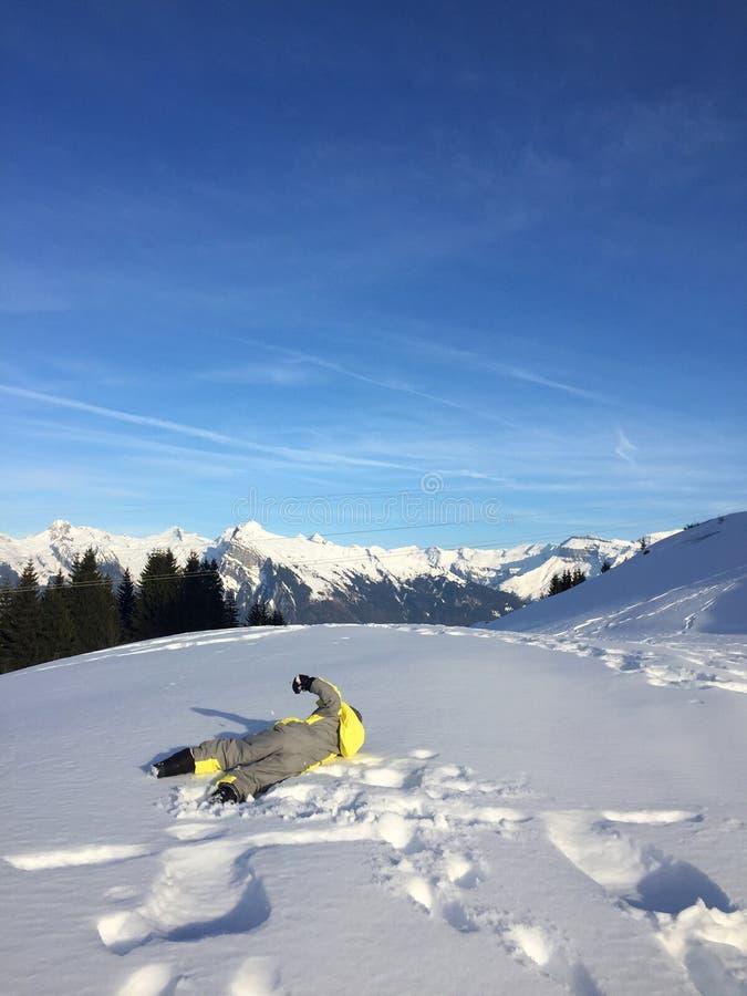 Kind im gelben Snowsuit, der im Schnee, Alpes, Frankreich spielt lizenzfreie stockfotos
