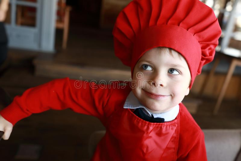 Kind im roten Kappenkoch stockfotos