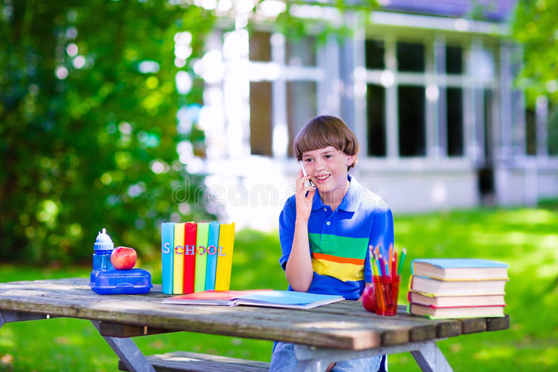 Kind im Schulhof studierend und am Telefon sprechend lizenzfreies stockfoto