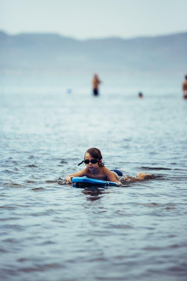 Kind im Schutzbrillenschwimmen auf bodyboard lizenzfreie stockbilder