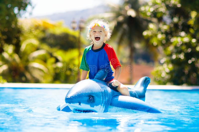 Kind im Swimmingpool Kind auf aufblasbarem Floss stockfotos