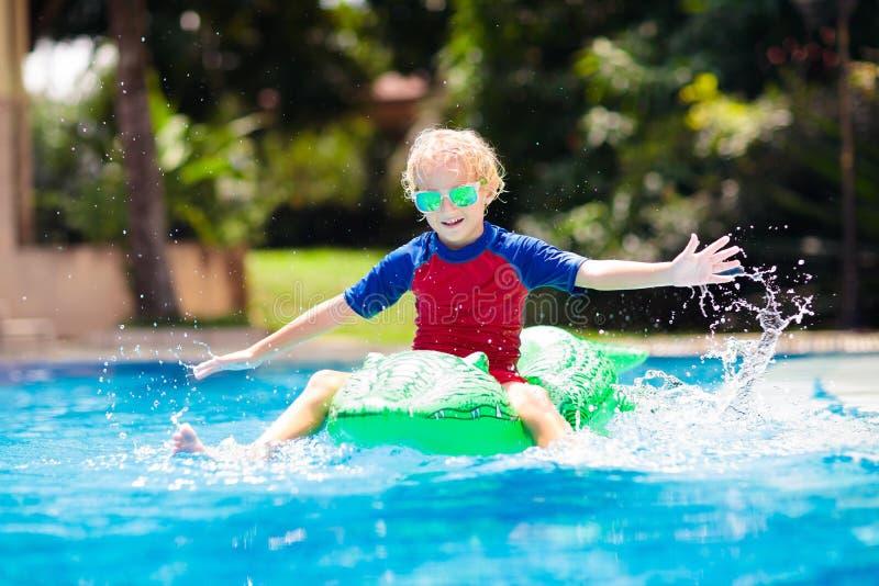 Kind im Swimmingpool Kind auf aufblasbarem Floss lizenzfreies stockbild
