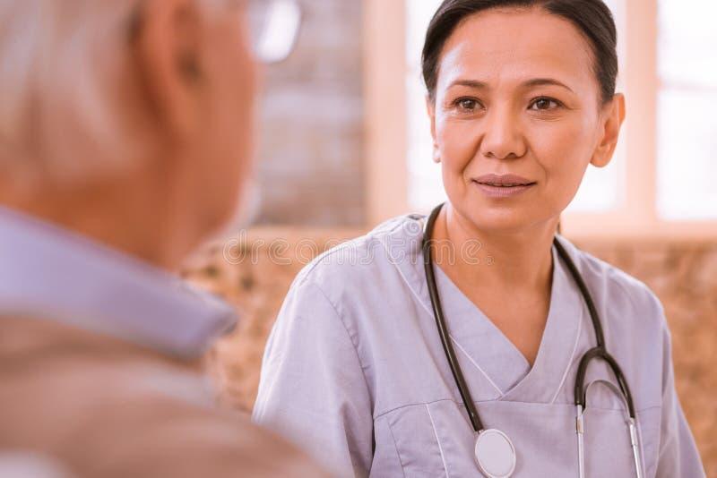 Kind international female having pleasant talk with patient stock photo