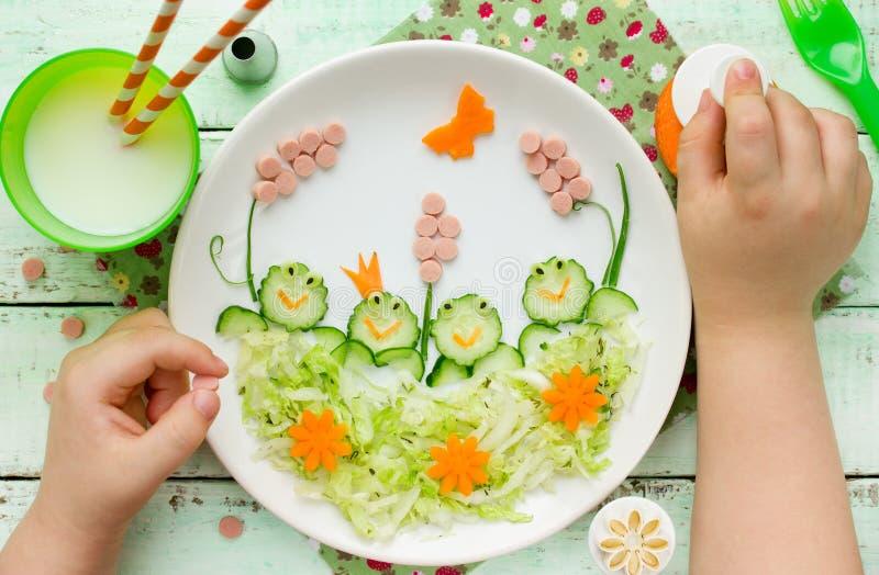 Kind isst eine gesunde Mahlzeit - Gurkenfrösche auf Kohlsalat lizenzfreie stockfotos