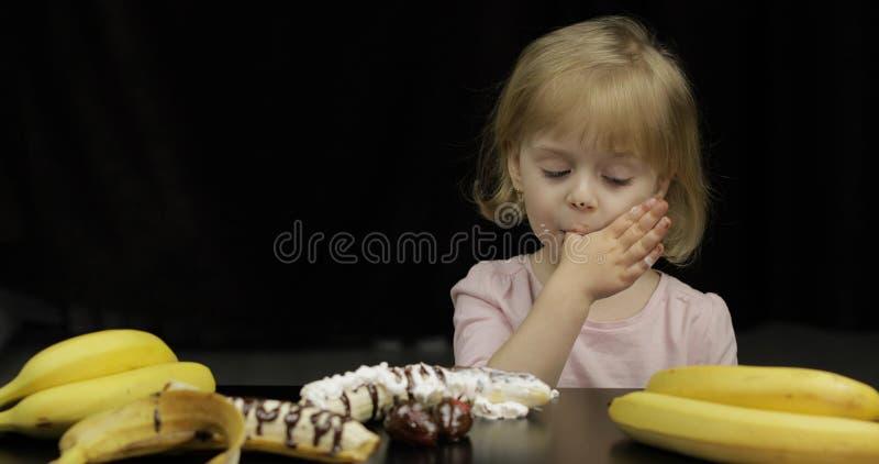 Kind isst geschmolzene Schokolade und Schlagsahne Schmutziges Gesicht lizenzfreie stockfotografie