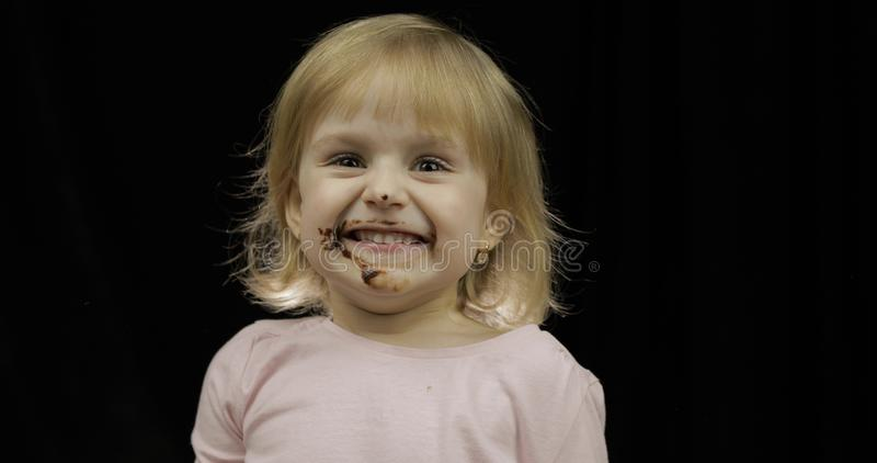 Kind isst geschmolzene Schokolade und Schlagsahne Schmutziges Gesicht stockbilder